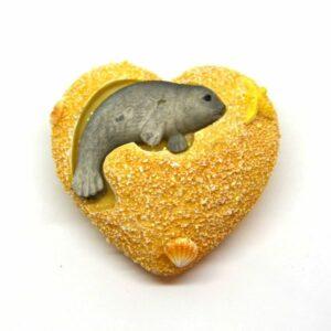Kerámia szív figurán homokos tengerpart fókával